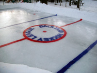 An ice rink with painted with blue lines and a red center line, complete with face-off circle. In the face-off circle is written backyard hockey league