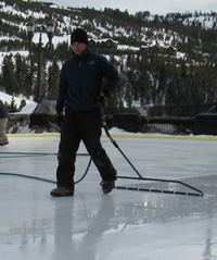A man holding a rink resurfacer